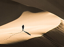 Lone person walking through vast desert sand dunes