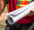 Construction person holding rolled-up drafting papers