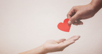 A person's hand placing a paper heart in the outstretched hand of another person