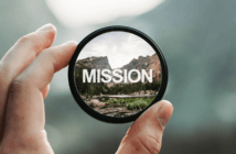 Photographer's loupe bringing into sharp focus a distant mountain range and the word MISSION