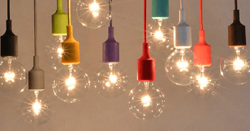 Many smaller lit lightbulbs hanging from colored cords