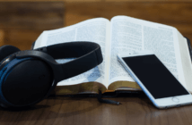 Headphones, a cell phone, and an open Bible