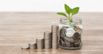 Stacks of coins increasing in height and a seedling growing from a small vase filled with coins