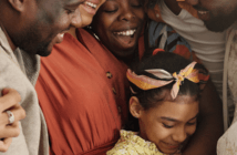 Group of people of different ages smiling and embracing at church