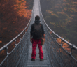 Person walking across a very long and very high pedestrian swinging bridge