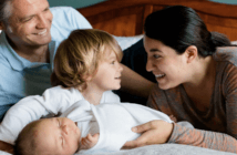 Smiling parents introducing their young smiling child to their infant