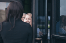 Person being warmly welcomed through a church's front doors by church memebers
