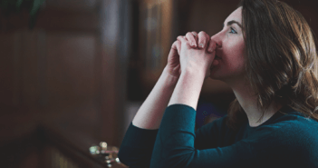 Person kneeling in prayer at the front of a church sanctuary